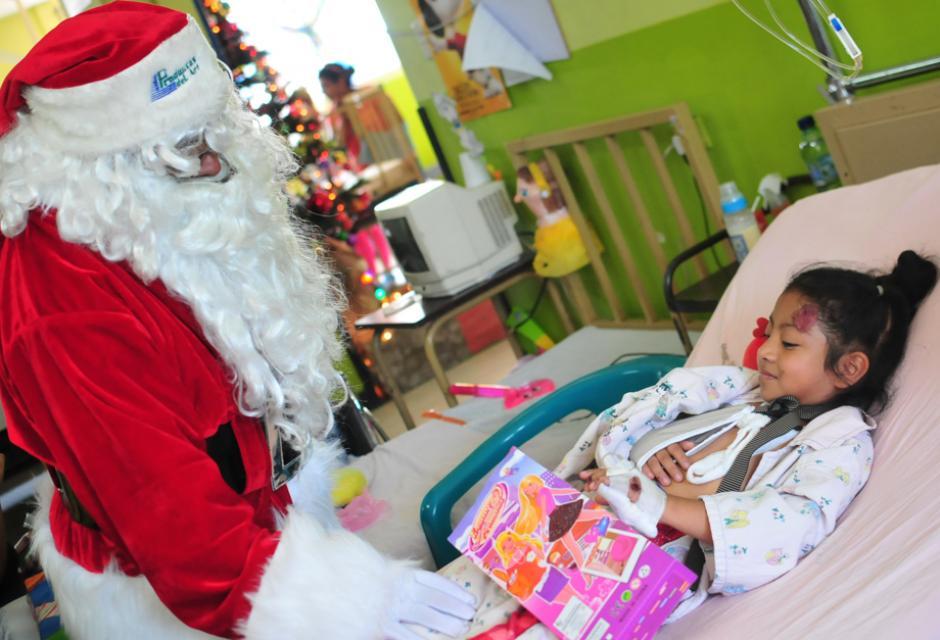 Niña interna de pediatría sonríe con Santa Claus al recibir una muñeca, como regalo de navidad (Foto: Alejandro Balán/Soy502)