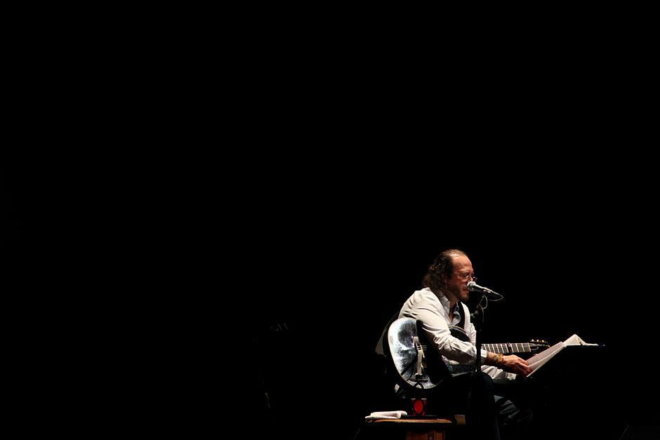 Fernando Delgadillo busca en sus apuntes la siguiente canción. Como es habitual en sus conciertos contó historias y chistes que fueron aplaudidos por el público. (Foto: Alexis Batres/Soy502)