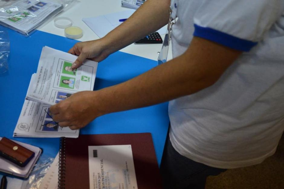Un integrante de la Junta Receptora de Votos, ordena las papeletas previo al inicio del conteo. (Foto:Jesús Alfonso/Soy502)