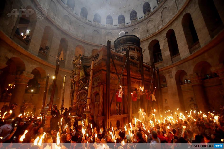 """Los fieles ortodoxos cristianos encienden velas en la iglesia del Santo Sepulcro en la ciudad de Jerusalén durante la ceremonia del """"Fuego sagrado"""" en la víspera de la Pascua ortodoxa. AFP Photo/Gali Tibbon (Tradu"""