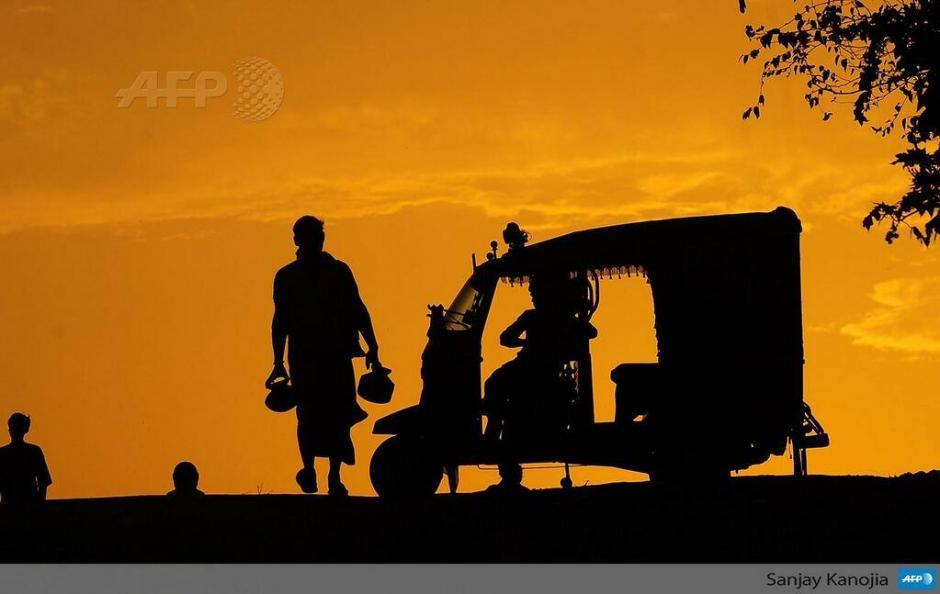 """El conductor de un """"rickshaw"""" indio espera pasajeros en Sangam durante una tormenta de polvo en Allahabad. (Foto: AFP)"""