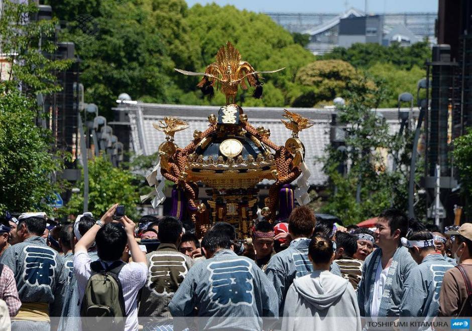 """Devotos japoneses llevan un santuario portátil llamado un """"Mikokshi O"""" durante el festival Sanja en Tokio.El evento de tres días de duración atrae millones de visitantes al distrito Asakusa de Tokio y es uno de los tres grandes festivales de Shinto en la capital japonesa. (Foto: AFP)"""
