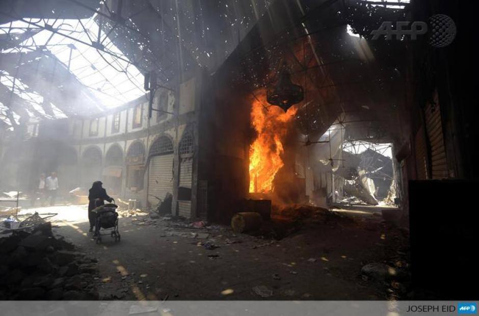 Una mujer empuja un carruaje al pasar por una tienda que arde en llamas en el mercado de Maskuf en la vieja ciudad de Homs, Siria. (Foto: AFP)