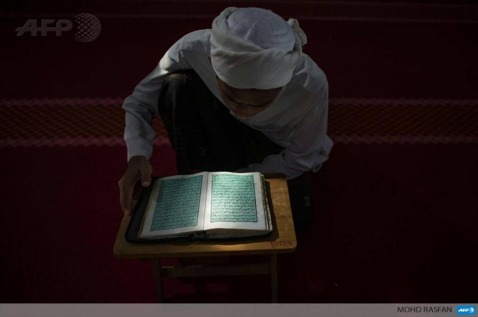 Una estudiante de la religión lee el Corán en una escuela de Malasia durante el mes de ayuno sagrado musulmán del Ramadán. (Foto: AFP)