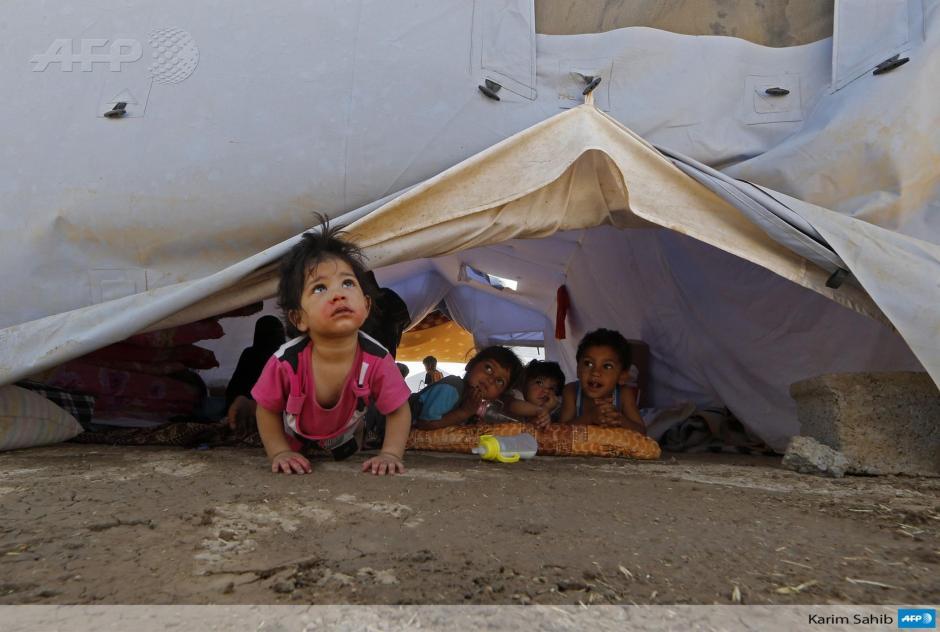 Los niños y niñas iraquíes desplazados permanecen dentro de una tienda de campaña en un campamento temporal instalado por la ACNUR para alojar a las personas que huyen de la violencia en el norte de Iraq. (Foto: AFP)