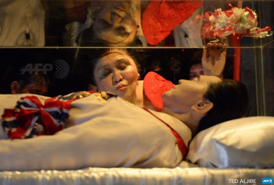 La ex primera dama filipina y ahora diputada Imelda Marcos besa la vitrina de su difunto marido y quien fuera presidente de Filipinas, Ferdinand Marcos, durante una visita a su mausoleo en su 85 º cumpleaños en la ciudad de Batac, Ilocos norte, al norte de Manila hoy. (Foto: AFP)