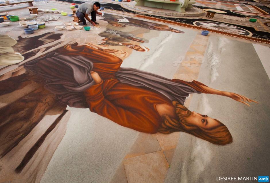 Éste es el trabajo de los creadores de una gran imagen de Cristo, realizada con tierra volcánica para celebrar Corpus Christi, en El Parque Nacional de El Teide en la ciudad de La Orotava, Tenerife, España. (Foto: AFP)