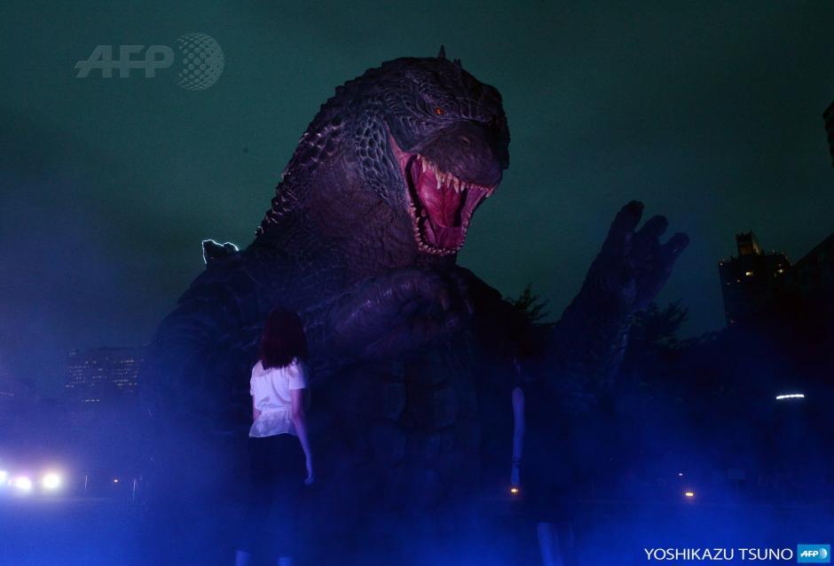 Una estatua de Godzilla de 6,6 metros de altura está iluminada en el parque de Midtown en Tokio para la promoción de la reciente película de Godzilla. (Foto: AFP)