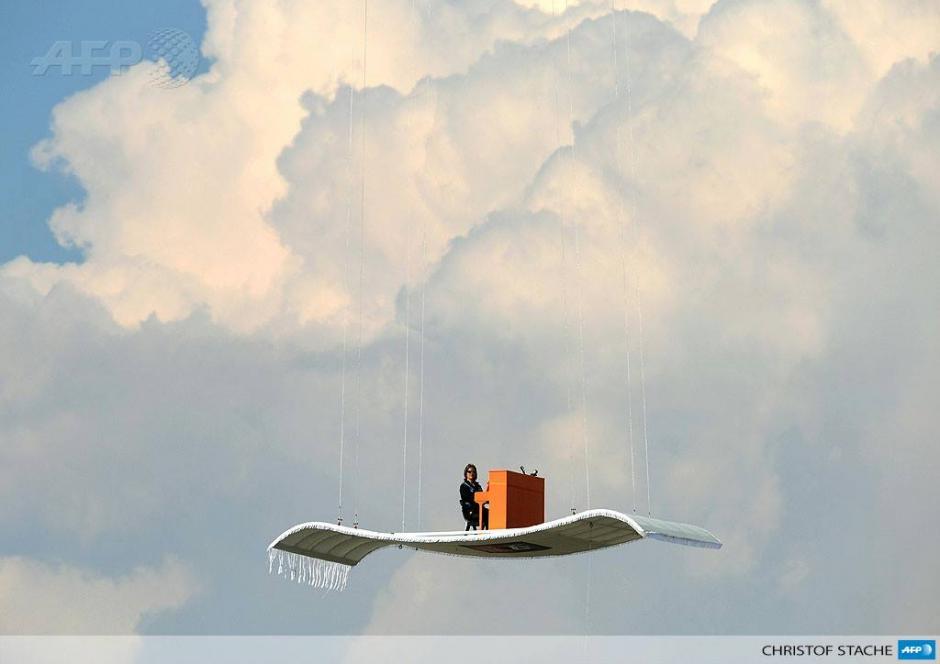"""El pianista Alemán Stefan Aarón se sitúa por encima del aeropuerto de Munich Franz Josef Strauss, tocando su piano de aluminio """"alfombra voladora"""" suspendido desde un helicóptero. La apariencia fue la cuarta parada de su tour """"Orange Piano"""". (Foto: AFP)"""