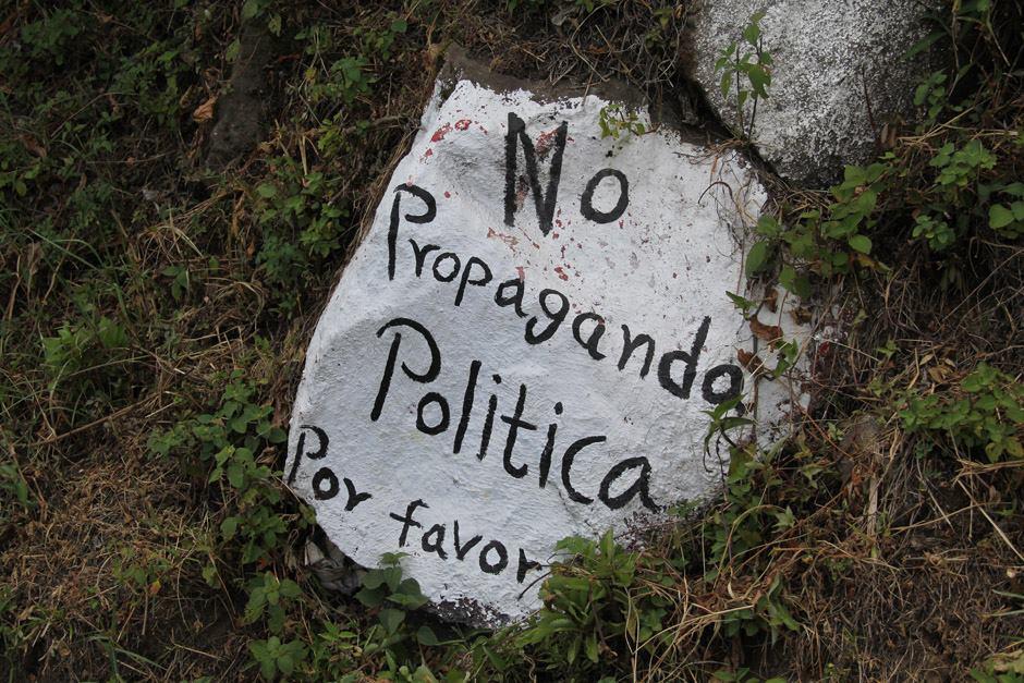 """Al salir del pueblo de Santiago Atitlán y enfilar la ruta hacia San Pedro la Laguna, se observa a la derecha el majestuoso lago que cautiva la vista. Hacia la izquierda piedras pintadas de blanco piden por favor a los políticos """"No propaganda política"""". (Foto: Alexis Batres/Soy502)"""