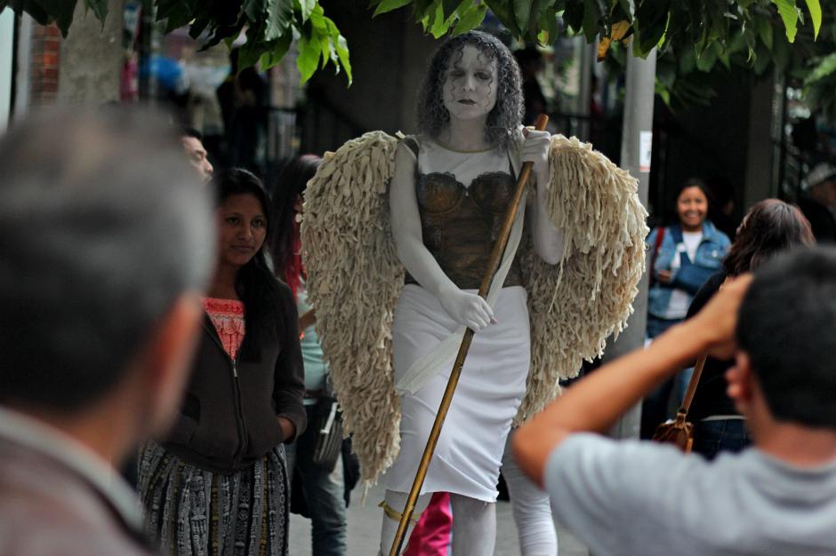 Personas toman fotografías a la estatua de San Miguel Arcángel.