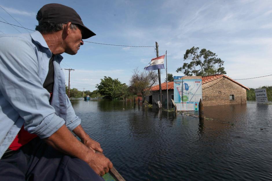 Vista de un hombre que se desplaza en canoa por un barrio de Asunción (Paraguay). (Foto: EFE)