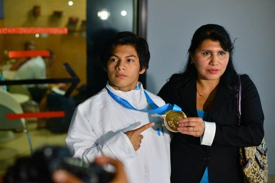Jorge Vega muestra la medalla de oro ganada en los Juegos Panamericanos de Toronto junto a Ángela López, su señora madre. (Foto: Wilder López/Soy502)