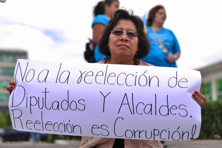 Una manifestante muestra una pancarta en contra de la reelección de diputados y alcaldes. (Foto Soy502: Wilder López)