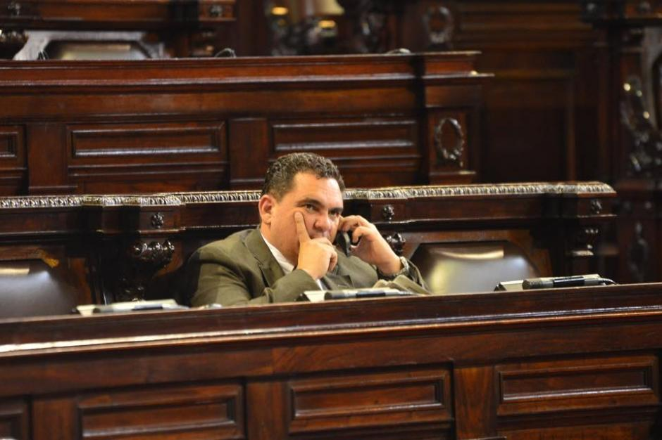Un diputado habla por teléfono mientras otros legisladores se presentan al Congreso de la República. (Foto: Jesús Alfonso / Soy502)