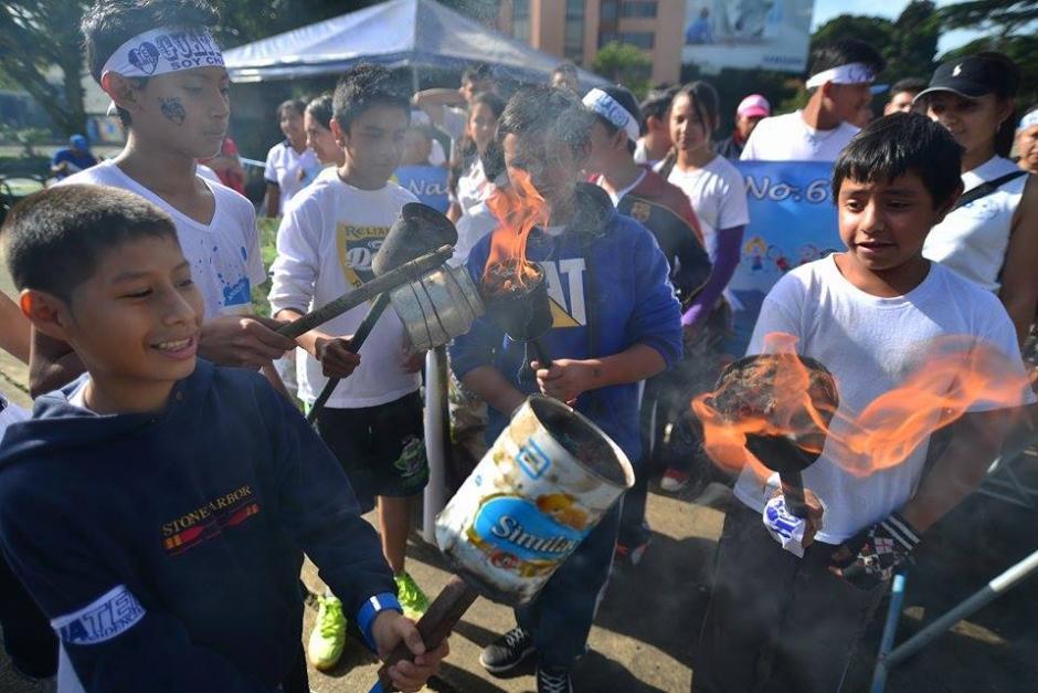 Varios estudiantes comparten la llama para sus respetivas antorchas, elaboradas artesanalmente con objetos reciclados.(Foto: Wilder López/Soy502)