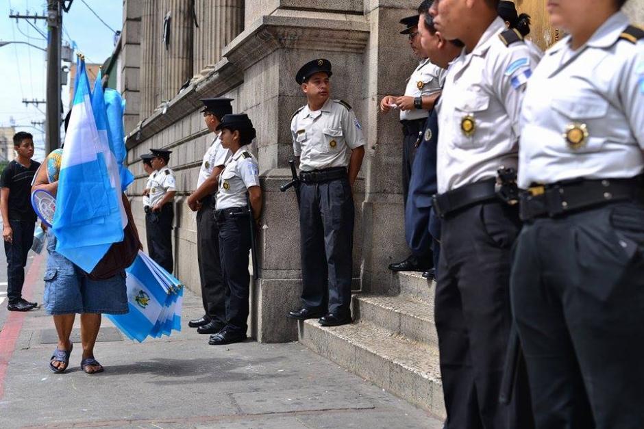 Una comerciante de banderas pasa frente al Congreso de la República que esta siendo resguardado por agentes de la Policía Nacional Civil. (Foto: Wilder López /Soy502)