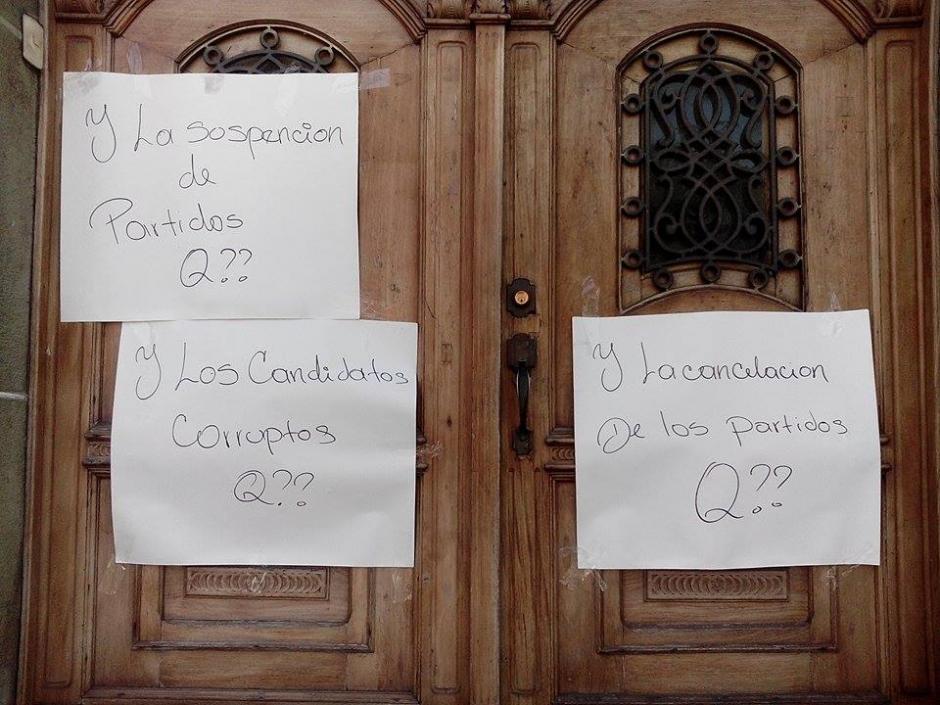 Manifestantes colocan carteles en las afueras del Tribunal Supremo Electoral. (Foto: Alejandro Balan/Soy502)