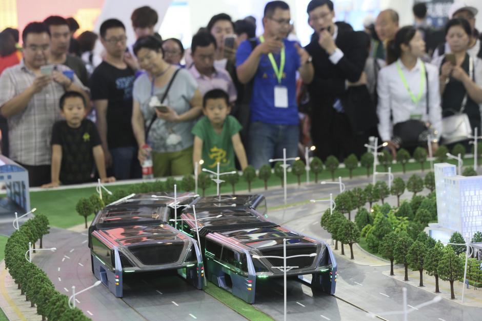 Fotografía que muestra a varios visitantes mientras observan la maqueta de un autobús que circularía sobre los carros para evitar los atascos. (Foto: EFE/Archivo)