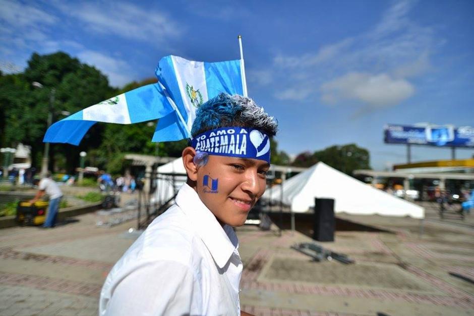 Un muchacho se pinta el pelo, se coloca una cinta en la frente y porta banderas azul y blanco para demostrar su amor por Guatemala.(Foto: Wilder López/Soy502)