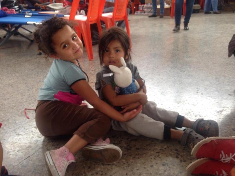 Dos niñas reciben un peluche que una empresa de ropa usada llevó al albergue en Santa Catarina Pinula. (Foto: Fredy Hernández/Soy502)