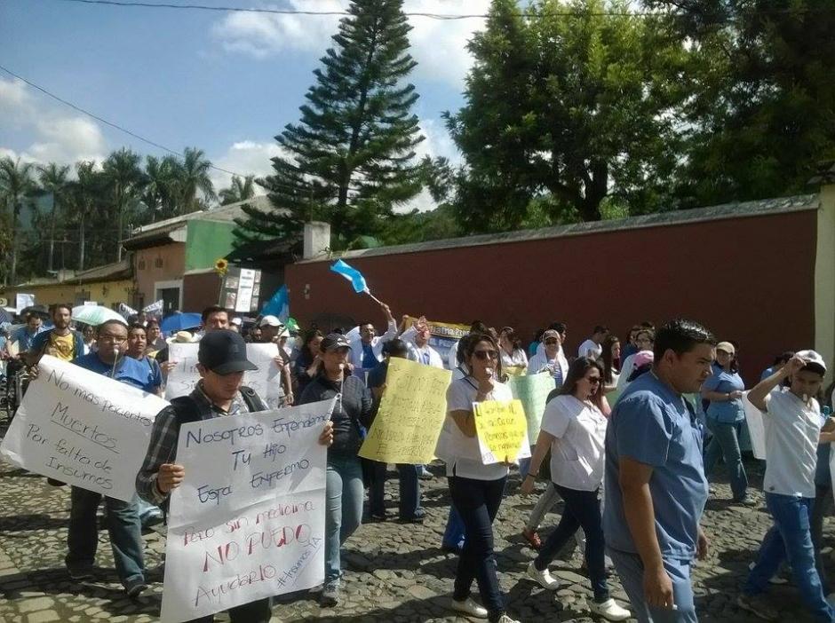 """""""No más pacientes muertos por falta insumos"""" se lee en algunos de los rótulos que portan los médicos y personal del hospital Pedro de Bethancourt de Antigua Guatemala. (Foto: Pedro Samayoa/ Bomberos ASEI )"""