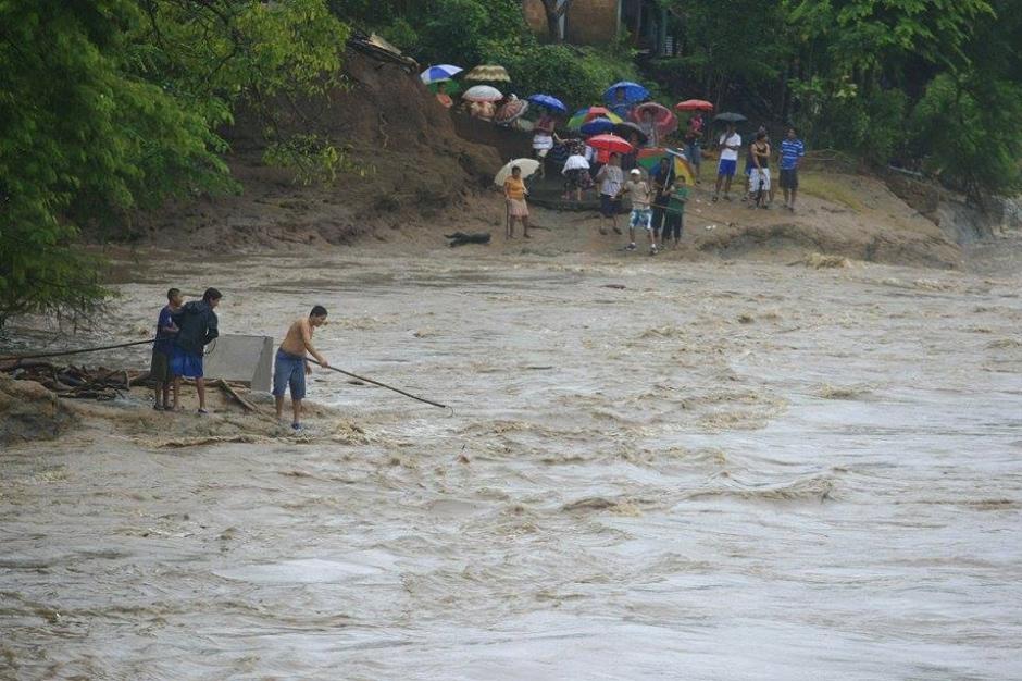 El Rio Paz también aumentó su caudal debido al aumento de lluvias en la región. Personas toman riesgos innecesarios cerca de las corrientes de los rios, algo que las instituciones de seguridad recomiendan no realizar. (Foto: Giovanni Lemus/Elperiodista.com.sv)