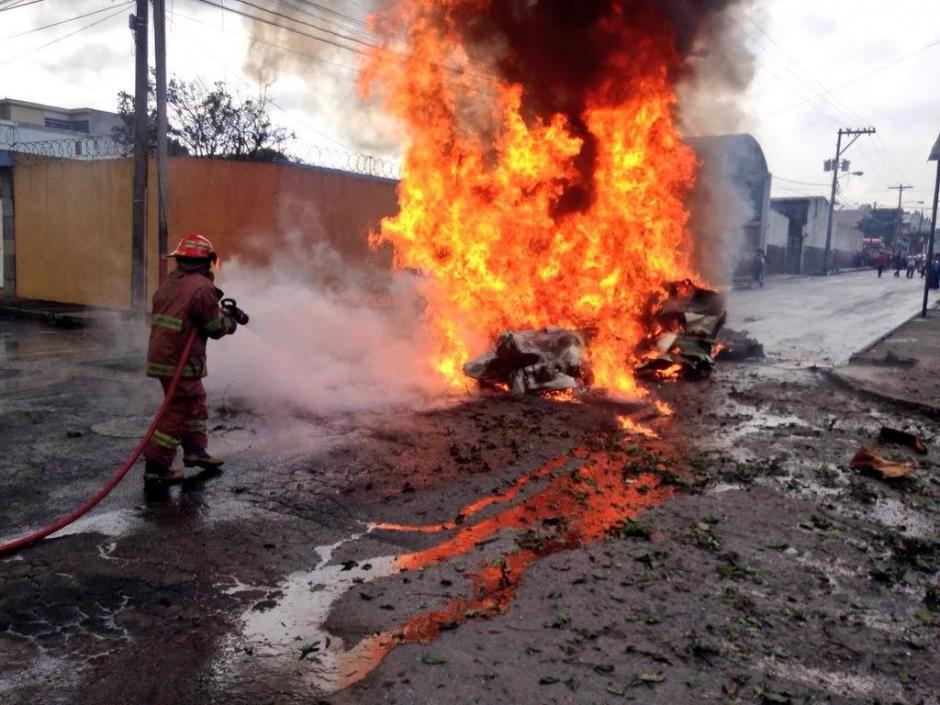 Los bomberos sofocaron el fuego de la avioneta incendiada tras el impacto en la zona 13. (Foto: Bomberos Municipales)