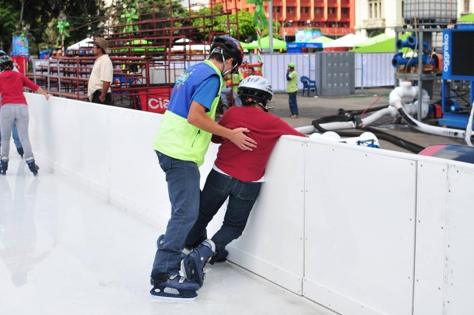 Un empleado municipal ayuda a uno niño dentro de la pista de hielo, se recomienda que al caer se empuñen las manos y se queden de rodillas, un colaborador municipal llegará a auxiliarlo. (Foto: Alejandro Balán/Soy502)
