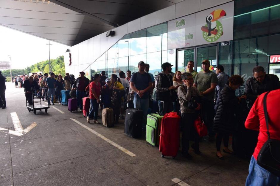 Largas filas de viajeros están a la espera de ingresar al Aeropuerto Internacional La Aurora por un bloqueo que realizan empleados del aeropuerto. (Foto: Jesús Alfonso/Soy502)