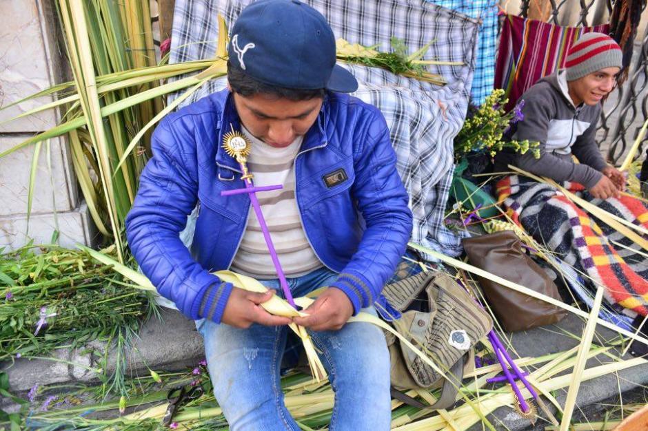 Joven alista las palmas de los feligreses. (Foto: Jesús Alfonso/Soy502)