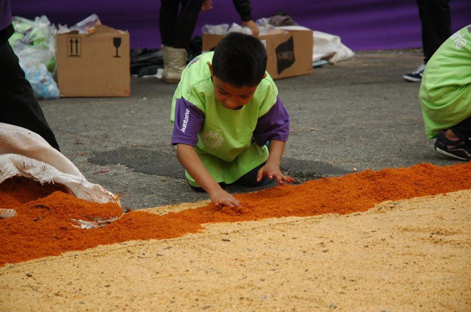 Desde los adultos hasta los más pequeños, la alfombra es el esfuerzo de decenas de guatemaltecos.  (Foto: Fredy Hernández/ Soy502)