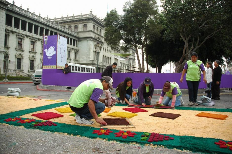 Con el Palacio Nacional de fondo, guatemaltecos elaboran la alfombra de aserrín en busca de un récord.  (Foto: Fredy Hernández/ Soy502)