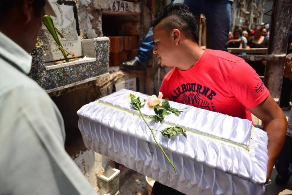 El féretro es depositado en el nicho del cementerio mientras los acompañantes brindan su apoyo a los apesarados familiares. (Foto: Jesús Alfonso/Soy502)