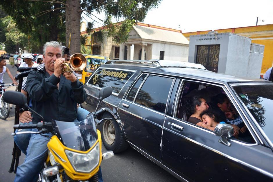 Un hombre con una trompeta hace más triste la partida del pequeño. (Foto: Jesús Alfonso/Soy502)
