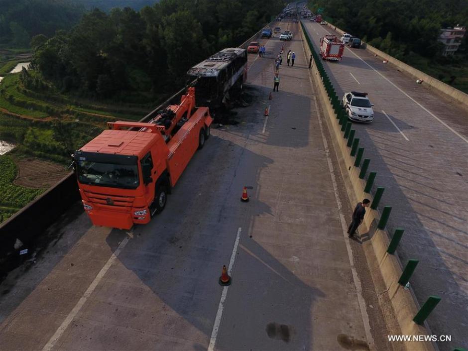 Una grúa llegó para remolcar el autobús incendiado. (Foto: Xinhua/Long Hongtao)