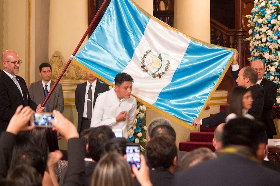 Los atletas pasan bajo la bandera durante la juramentación. (Foto: Alejandro Balán/Soy502)