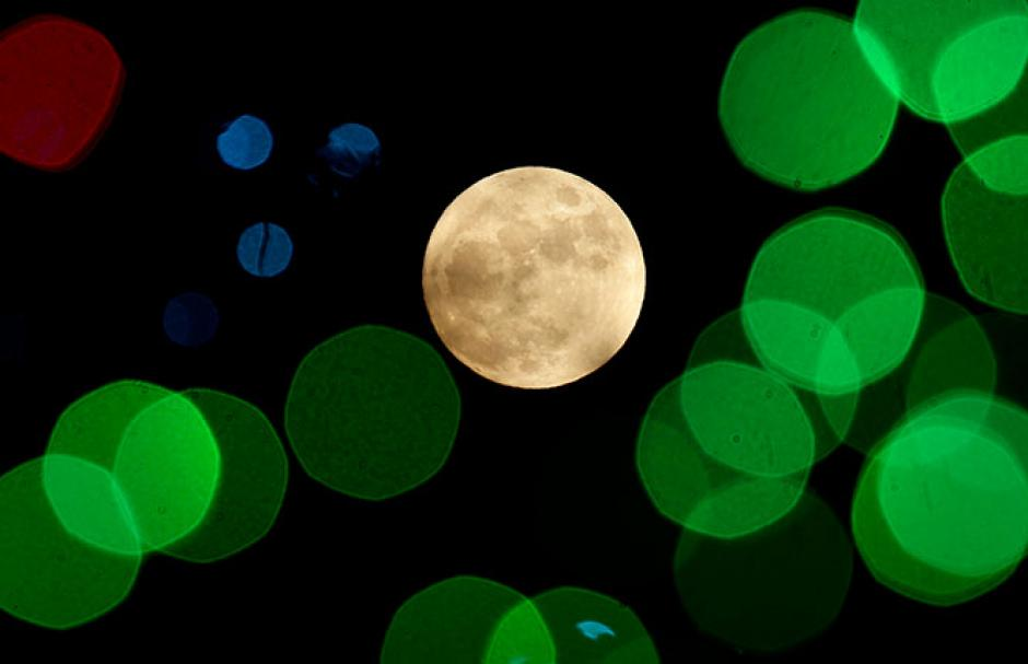 La luna se pierde entre las luces navideñas en Lenexa, Kansas. (Foto Cuartoscuro / Reuters y AP)