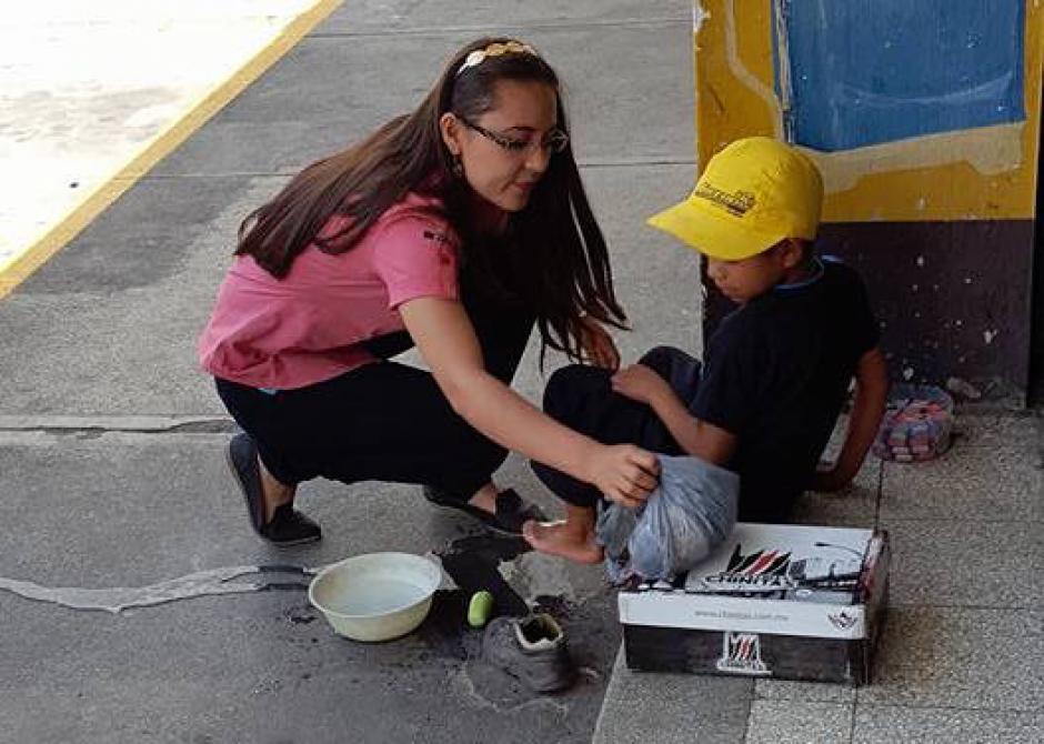 La buena samaritana sienta al niño en una grada para quitarle los zapatos viejos que llevaba. (Foto: Jhon Monsalve)