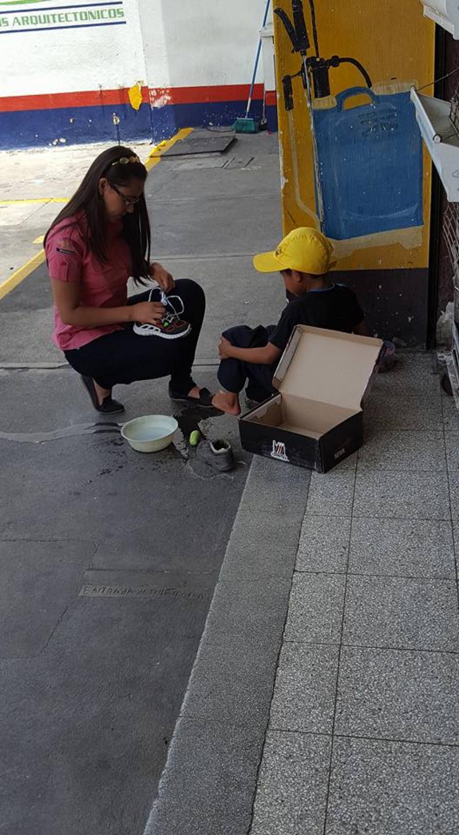 Con agua y jabón, la mujer se acerca al niño que ve sorprendido el acto solidario hacia él. (Foto: Jhon Monsalve)