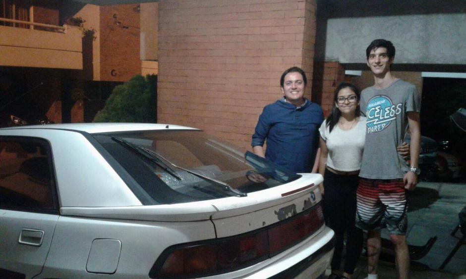 Alejandra Cáceres y Daniel Calderón lavan carros para recolectar dinero par un encuentro juvenil al que desean asistir. (Foto: Facebook, Pablo Mazariegos)