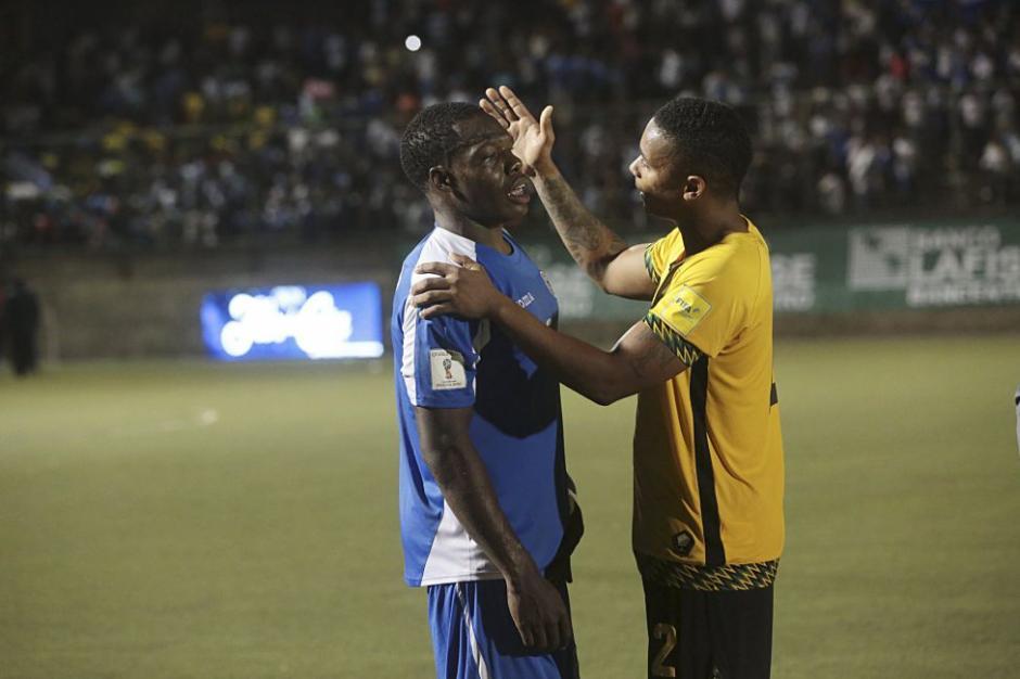 Un futbolista jamaiquino da aliento a su colega nicaragüense que llora tras la eliminación sufrida en casa.