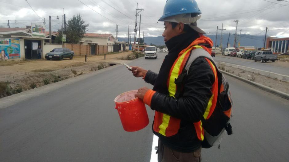 El ingenio y las ganas de salir adelante, hicieron que dos jóvenes encontraran la manera de ganarse unos centavos pintando las cinta asfáltica del Periférico de Quetzaltenango. (Foto: Carlos González/Stereo100Xela)
