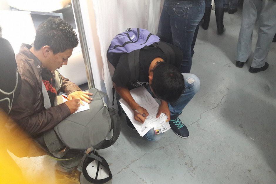 Muchos, al no encontrar espacio en una mesa se pusieron a llenar formularios en el suelo. (Foto: Javier Lainfiesta/Soy502)