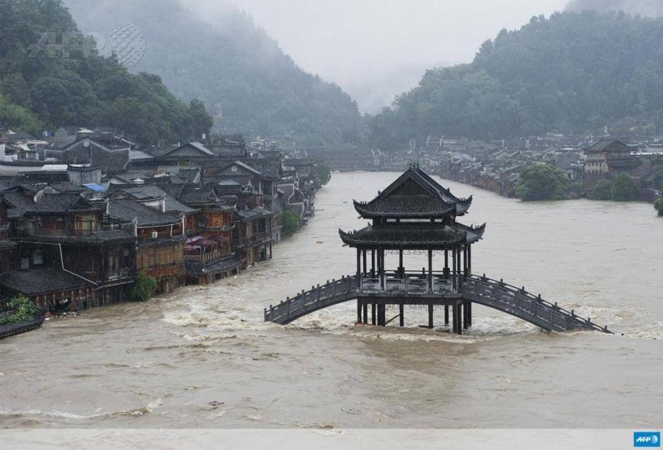 Inundaciones sumergen un puente en la población de Fenghuang, en la provinica central de Hunan en China. (Foto: AFP)