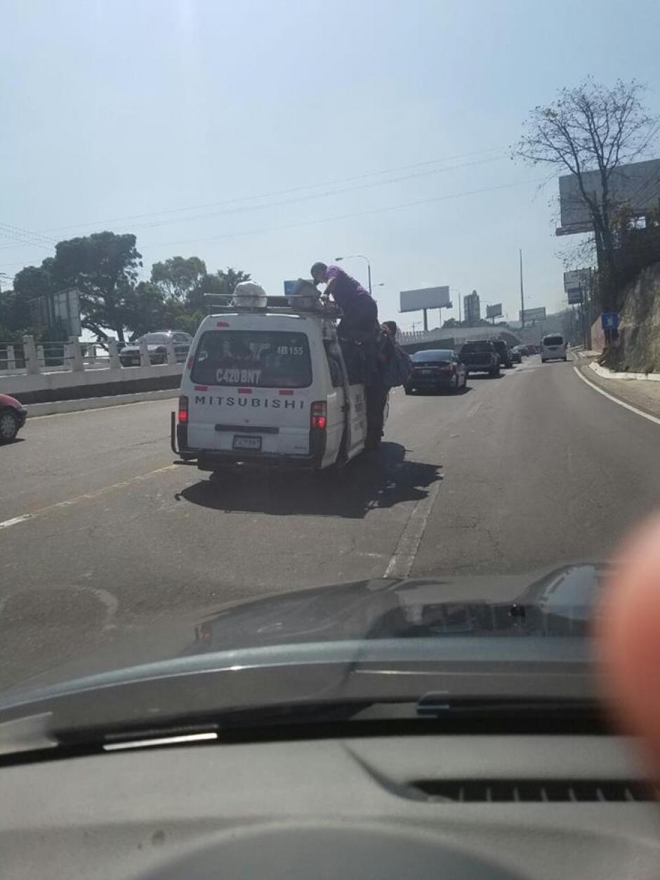 Pasajeros viajan sobre la parrilla de un microbús en Mixco. (Foto: Luis Reyes)