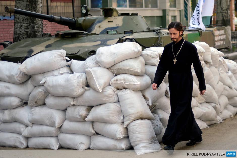 Un sacerdote ortodoxo pasa por el edificio regional del Servicio Seguridad que está tomado por los separatistas en la oriental ciudad ucraniana de Slavyansk.Los rebeldes Pro Kremlin en Ucrania se están preparando para una renovada ofensiva militar por Kiev. (Foto: AFP)