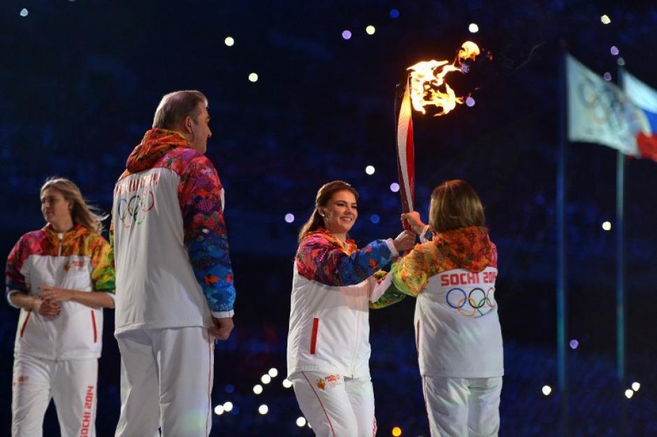 La medallista olímpica Alina Kabaeva le da la antorcha olímpica a Irina Rodnina previo a encender el fuego olímpico