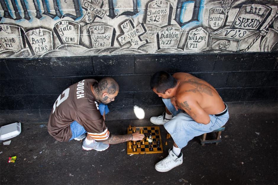 Dos hombres juegan ajedrez cerca de un mural donde están registrados los sobrenombres de sus compañeros que han fallecido defendiendo la causa de la Mara Salvatrucha.(Foto: Adam Hinton)