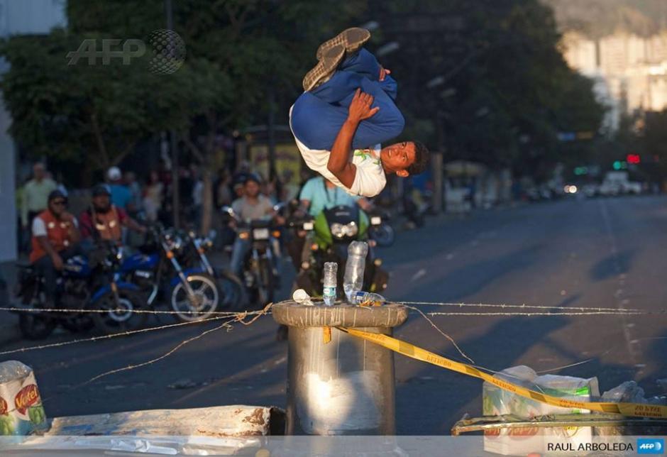 Un hombre salta una de las tantas barricadas que se han instalado en Caracas durante una de las protestas contra el gobierno del presidente Nicolás Maduro. (Foto: AFP)